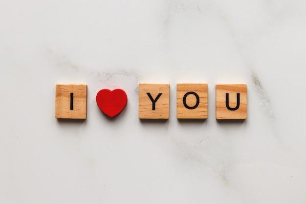Dia dos namorados e o conceito de amor. a inscrição eu te amo feita de letras de madeira e coração vermelho