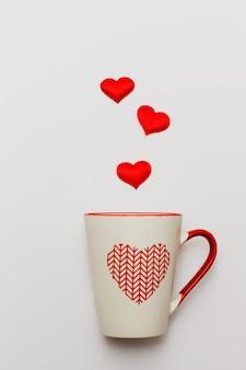 Dia dos namorados e o conceito de amor. corações vermelhos espirram do copo branco.