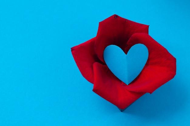 Dia dos namorados e oitavo de março, pétalas de rosa e coração em caixa em fundo azul