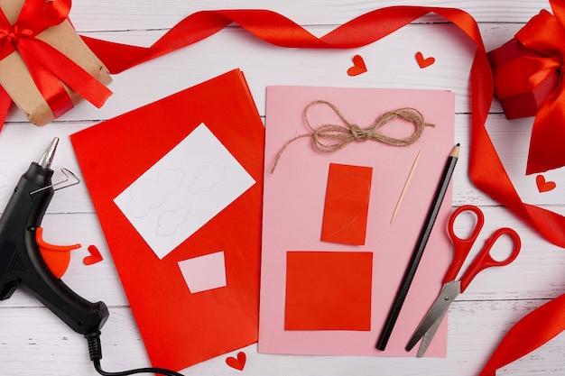 Dia dos namorados faça você mesmo. instruções passo a passo para cartão artesanal dos namorados com pára-quedas de corações. dom de artesanato, postura plana. passo 1