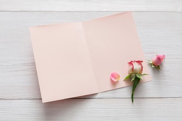 Dia dos namorados, flores de rosas cor de rosa e pétalas espalhadas na madeira rústica branca e um cartão aberto e vazio