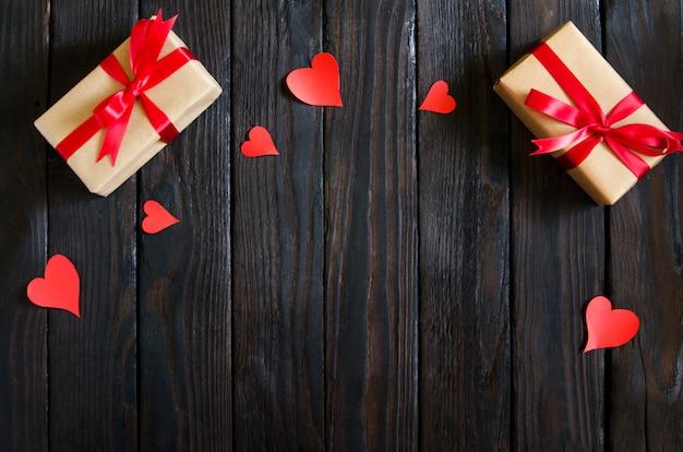 Dia dos namorados fundo de madeira com coração vermelho, presentes e velas. presentes para o dia dos namorados. fundo de madeira preto