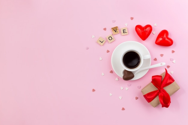 Dia dos namorados. fundo rosa com xícara de café, caixa de presente e velas. amor feito de letras de madeira