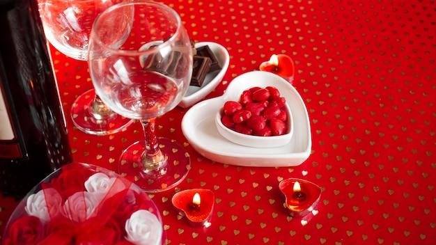 Dia dos namorados. garrafa de videira, copos, rosas vermelhas, velas - fundo vermelho. conceito de jantar de amor