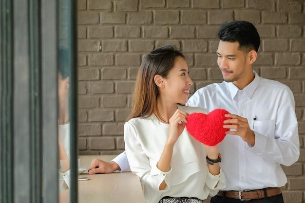 Dia dos namorados homem deu o coração vermelho para a menina para mostrar o amor.