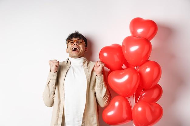 Dia dos namorados. homem moderno feliz comemorando, gritando de alegria e felicidade, tendo encontro com o amante, estar apaixonado, em pé perto de balões de coração em fundo branco.