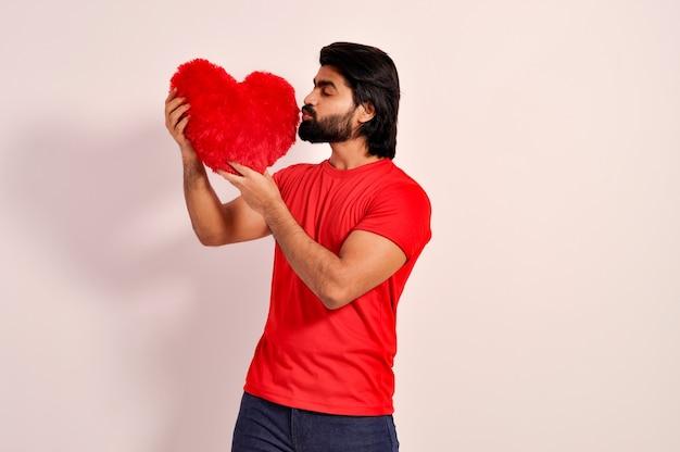 Dia dos namorados jovem indiano bonito segurando e beijando um travesseiro vermelho em forma de coração