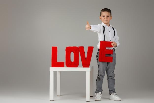 Dia dos namorados. menino elegante criança segurando palavras vermelhas letras de amor em fundo cinza.