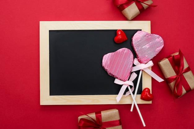 Dia dos namorados mock up, lousa com pirulito em forma de um coração, caixas de presente e glitter isolado sobre fundo vermelho, copie o espaço.