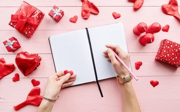 Dia dos namorados. mulher escrevendo em folhas de papel em branco na mesa de madeira rosa decorada com velas vermelhas dos namorados e presentes