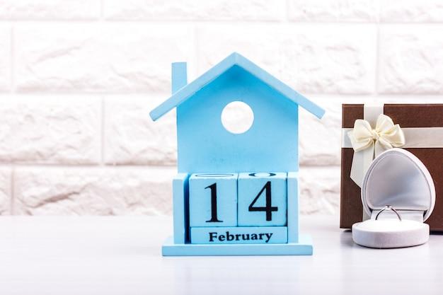 Dia dos namorados nos cubos do calendário com caixa de presente e anel de diamante