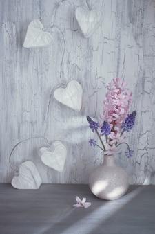 Dia dos namorados ou celebração da primavera, vaso com jacintos flores e guirlanda de luzes em forma de coração de papel em madeira rústica