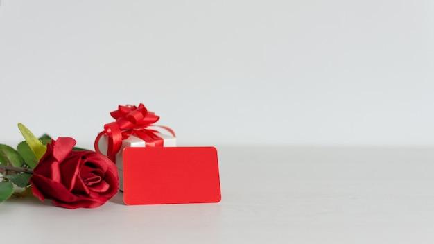 Dia dos namorados ou presente de aniversário e um monte de lindas rosas vermelhas com uma etiqueta de presente em branco vermelha anexada