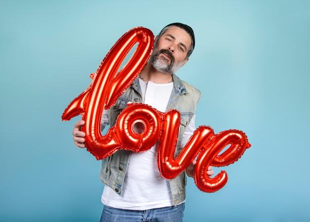 Dia dos namorados. palavra cartas de amor de insufláveis. homem gay barbudo segurando uma palavra grande amor com um grande sorriso sobre fundo azul.