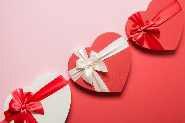 Dia dos namorados romântico corações presentes sobre fundo vermelho. postura plana. cartão com espaço de cópia.