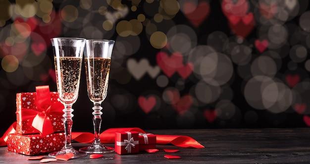Dia dos namorados. taças de champanhe, velas e corações vermelhos em um belo bokeh de fundo