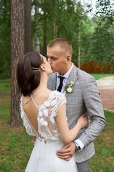 Dia dos namorados, um casal apaixonado se abraçando e beijando no parque. homem abraça mulher bonita, noivado