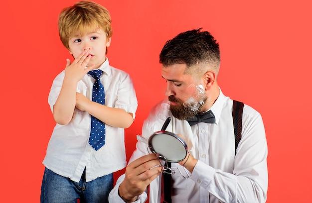 Dia dos pais. filho e pai barbeando a barba. tempo para a família. assistente para o pai. pequeno barbeiro. barbearia.