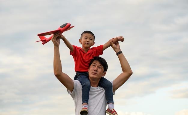 Dia dos pais. pai e filho brincando juntos ao ar livre avião de papel