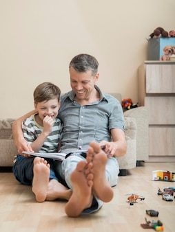 Dia dos pais pai e filho lendo um livro no chão
