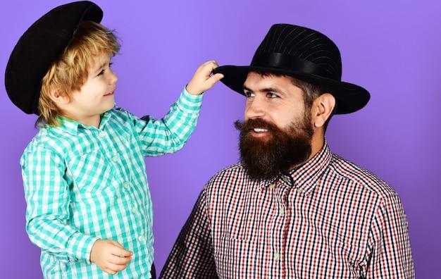Dia dos pais. pai feliz com o filho em camisas xadrez e chapéus na moda. conceito de paternidade.