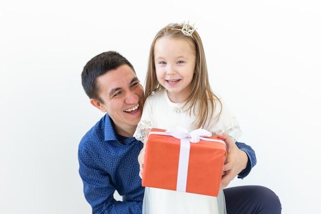 Dia dos pais, paternidade e conceito de família - pai abraça sua filha segurando uma caixa de presente vermelha sobre uma parede branca.