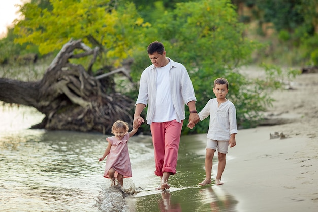 Dia dos pais. um homem bronzeado feliz caminha ao longo da margem do rio com seus filhos, filha e filho.