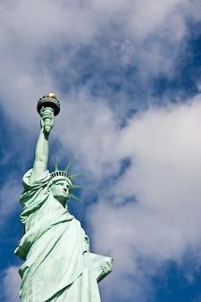 Dia ensolarado, céu azul com nuvens: estátua da liberdade com espaço de cópia