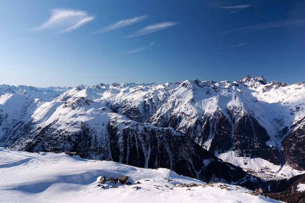 Dia ensolarado de inverno em estação de esqui alpina com céu azul e neve branca e brilhante Foto Premium