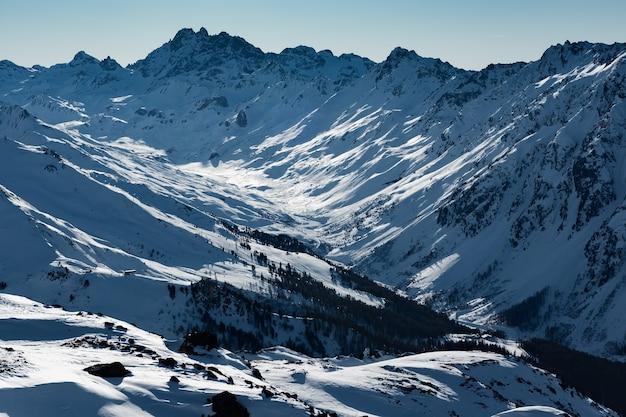 Dia ensolarado de inverno em estação de esqui alpina com céu azul e neve branca e brilhante