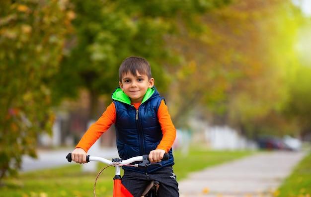 Dia ensolarado de outono. menino de bicicleta em um parque da cidade. o conceito de relaxamento e diversão no tempo. foto com muito espaço em branco.