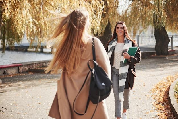 Dia ensolarado. dois jovens amigos ficam felizes em se conhecer no parque após o estudo