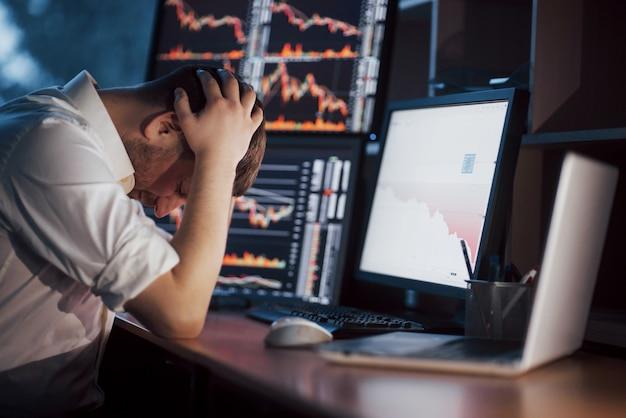 Dia estressante no escritório. jovem empresário de mãos dadas no rosto enquanto está sentado na mesa do escritório criativo. gráfico de finanças forex