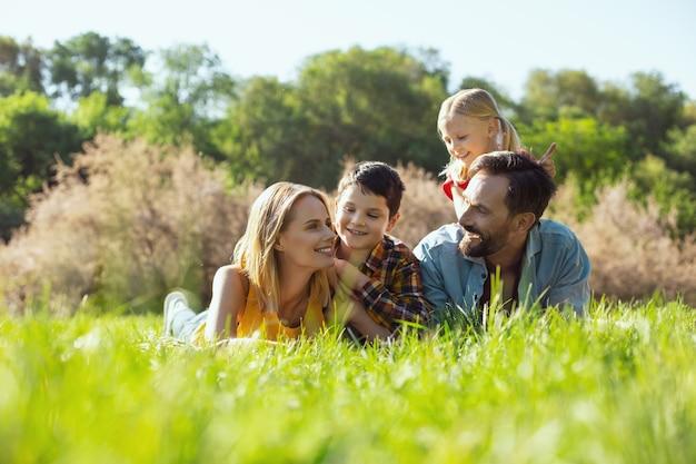 Dia incrível. mãe bonita e feliz deitada na grama com a família e sorrindo