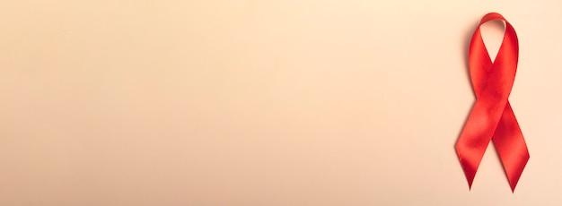 Dia internacional da aids. close up da fita vermelha em um fundo bege. banner. conceito de conscientização de aids. 1 de dezembro.
