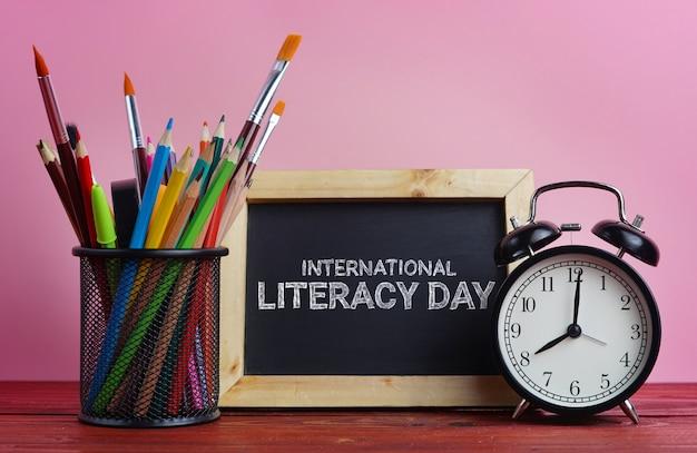 Dia internacional da alfabetização. quadro-negro, despertador e escola estacionária na cesta rosa