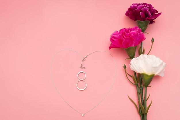 Dia internacional da mulher com flores e colar de forma de coração no fundo rosa
