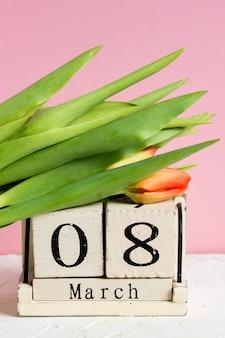 Dia internacional das mulheres. calendário de madeira 8 de março e tulipas vermelhas em fundo rosa