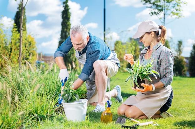 Dia juntos. esposa sorridente e amorosa vendo seu belo homem arrancando ervas daninhas enquanto passam o dia juntos