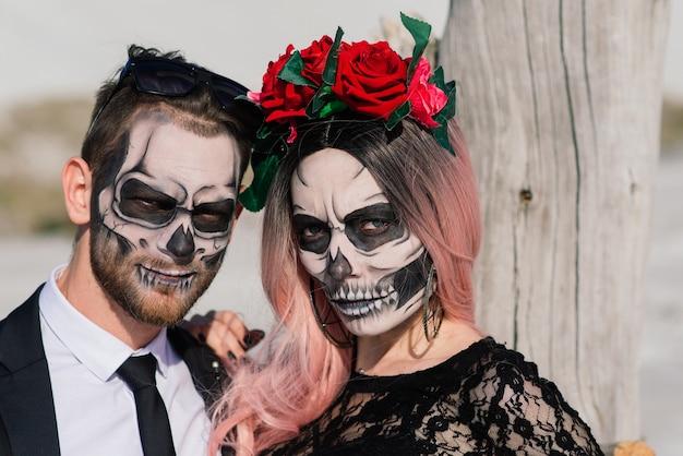 Dia malvado do casal morto-vivo posando, maquiagem de halloween