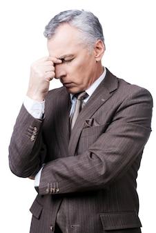 Dia muito estressante. homem maduro frustrado em trajes formais tocando a cabeça com os dedos e mantendo os olhos fechados, enquanto se apoia em um fundo branco