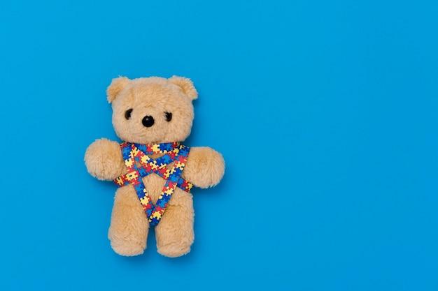 Dia mundial da conscientização do autismo, conceito de saúde mental com ursinho de pelúcia e padrão de quebra-cabeça de fita
