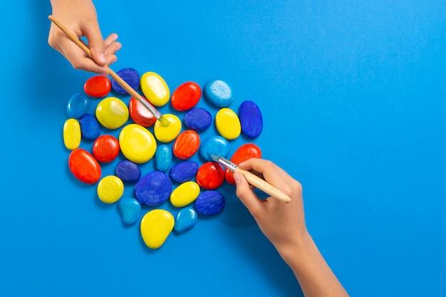 Dia mundial da conscientizaçao sobre o autismo. mãos de crianças pintando com coração de escovas feitas de pedras nas cores amarelas vermelhas azuis