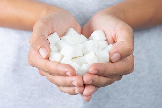 Dia mundial da diabetes; mão segurando cubos de açúcar