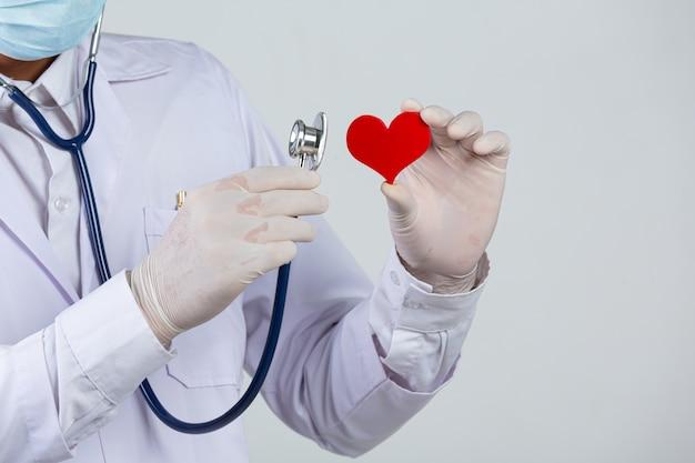 Dia mundial da diabetes; médico segurando um estetoscópio e um coração vermelho em forma de madeira