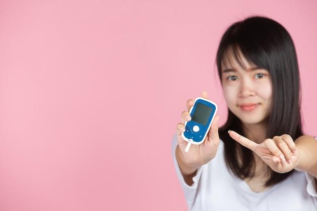 Dia mundial da diabetes; mulher segurando o medidor de glicose na parede rosa