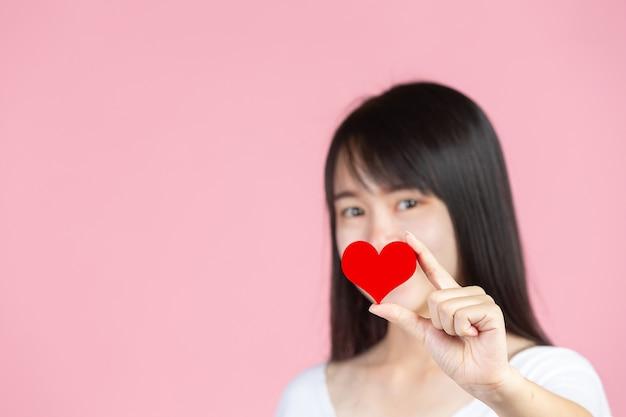 Dia mundial da diabetes; mulher segurando um coração vermelho na parede rosa