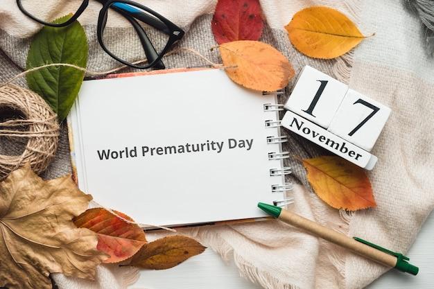 Dia mundial da prematuridade. 17 de novembro em calendário feito de cubos brancos em manta com caderno e folhas. manta plana