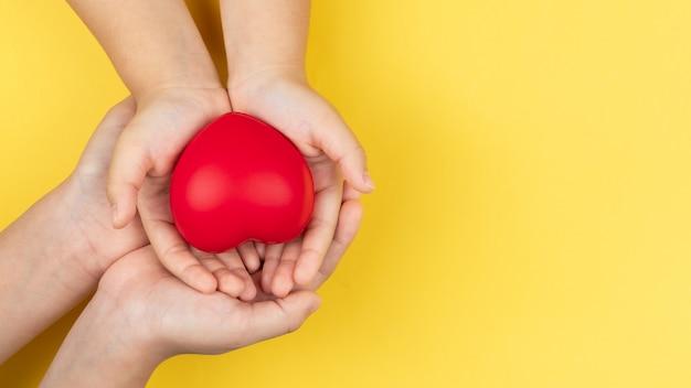 Dia mundial da saúde, adulto e criança mãos segurando coração vermelho, cuidados de saúde, amor e conceito de seguro familiar