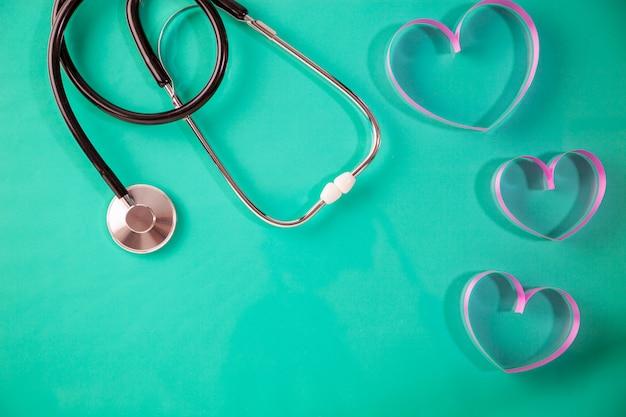 Dia mundial da saúde, cuidados de saúde e conceito de fundo médico do estetoscópio com fita de coração no papel verde, copie o espaço para seu texto.